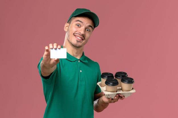 Männlicher kurier der vorderansicht in der grünen uniform, die braune kaffeetassen und karte mit lächeln auf rosa hintergrund hält