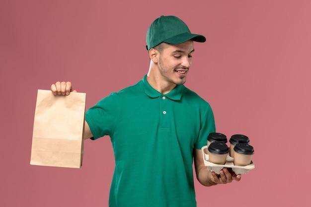 Männlicher kurier der vorderansicht in der grünen uniform, die braune kaffeetassen und lebensmittelpaket auf dem rosa hintergrund hält