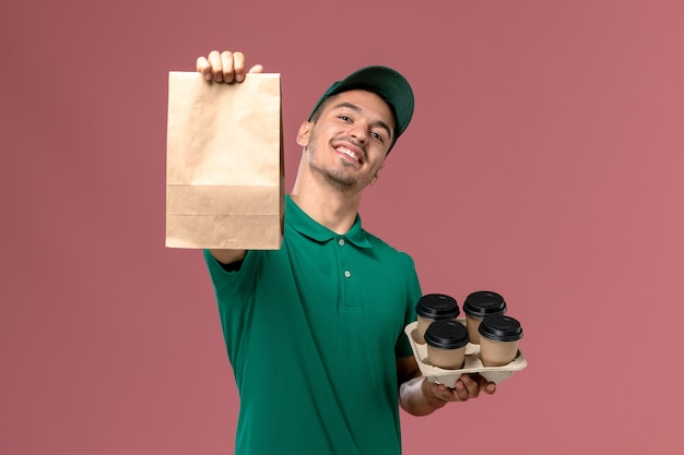 Männlicher kurier der vorderansicht in der grünen uniform, die braune kaffeetassen und lebensmittelpaket auf hellrosa hintergrund hält