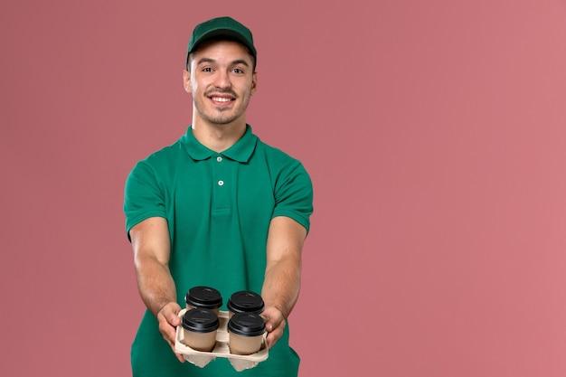 Männlicher kurier der vorderansicht in der grünen uniform, die die kaffeetassen der lieferung hält, die sie auf rosa hintergrund liefern