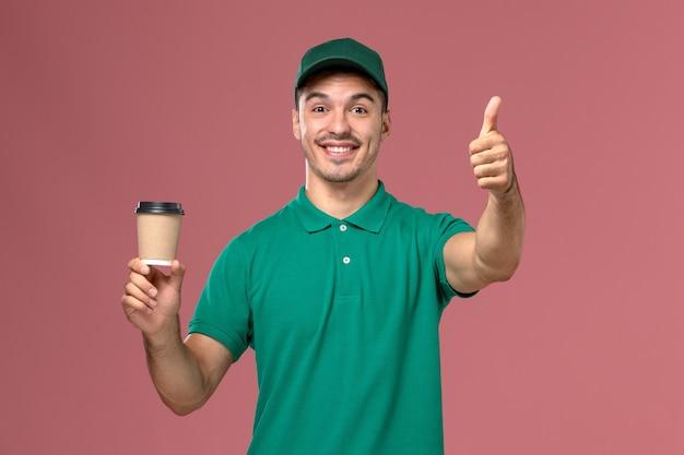 Männlicher kurier der vorderansicht in der grünen uniform, die kaffeetasse auf dem rosa schreibtisch lächelt und hält