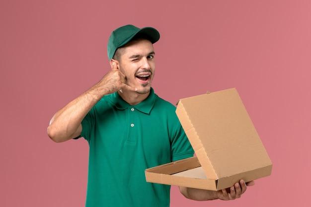 Männlicher kurier der vorderansicht in der grünen uniform, die lebensmittelbox hält und öffnet, die auf rosa hintergrund zwinkert