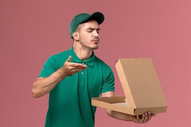 Männlicher kurier der vorderansicht in der grünen uniform, die lebensmittelbox hält und öffnet, die es auf rosa hintergrund riecht