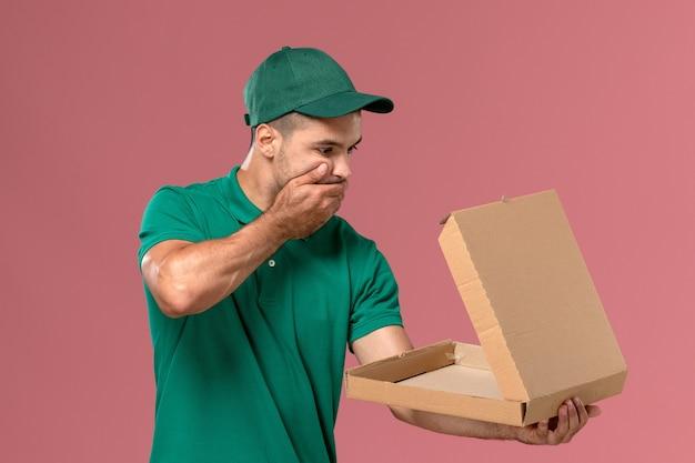 Männlicher kurier der vorderansicht in der grünen uniform, die lebensmittelbox mit schockiertem ausdruck auf rosa hintergrund hält und öffnet