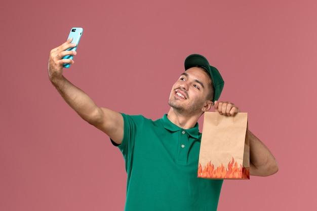 Männlicher kurier der vorderansicht in der grünen uniform, die lebensmittelpaket hält und foto mit ihm auf dem rosa hintergrund macht