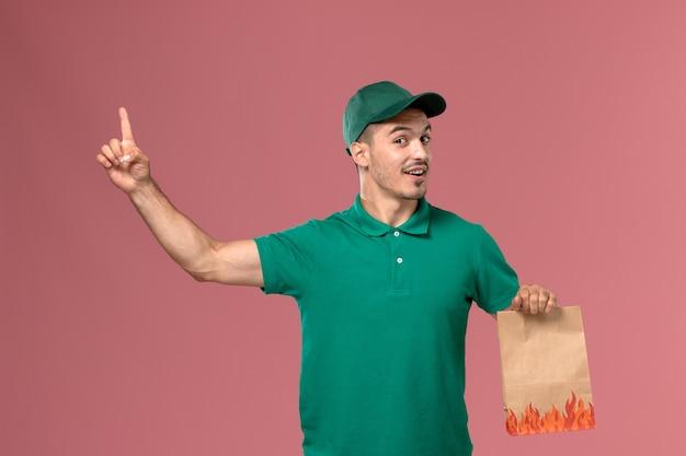 Männlicher kurier der vorderansicht in der grünen uniform, die lebensmittelpaket hält und mit erhöhtem finger auf hellrosa hintergrund posigniert