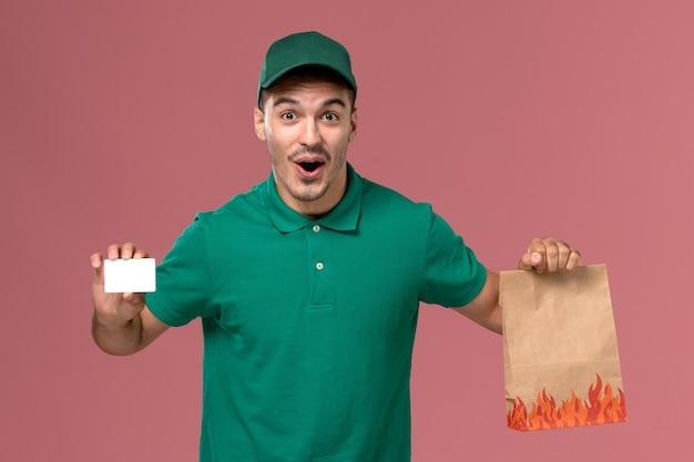 Männlicher kurier der vorderansicht in der grünen uniform, die lebensmittelpaket und karte auf dem rosa hintergrund hält
