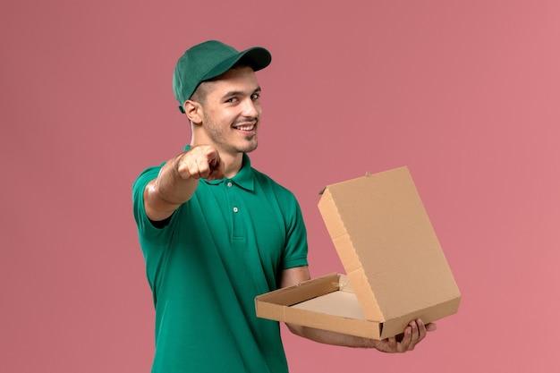 Männlicher kurier der vorderansicht in der grünen uniform, die nahrungsbox auf dem hellrosa hintergrund hält und öffnet