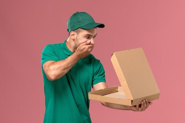 Männlicher kurier der vorderansicht in der grünen uniform, die nahrungsbox auf hellrosa hintergrundmann hält und öffnet
