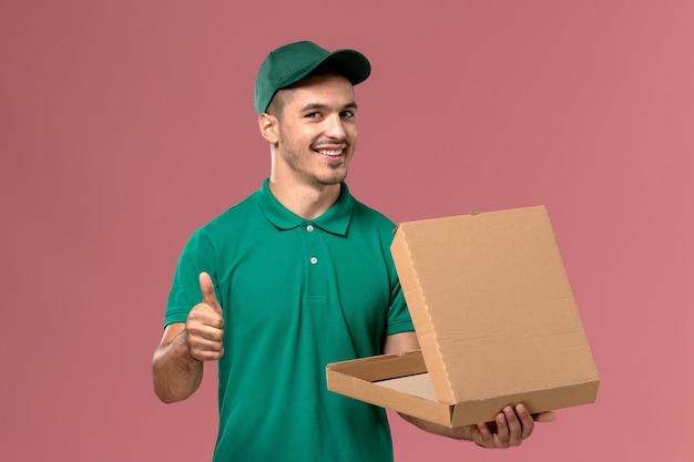 Männlicher kurier der vorderansicht in der grünen uniform, die nahrungsbox auf rosa hintergrund hält und öffnet