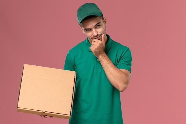 Männlicher kurier der vorderansicht in der grünen uniform, die nahrungsmittelbox denkt, der auf dem rosa hintergrund denkt