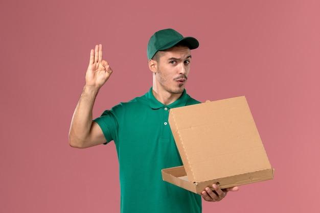 Männlicher kurier der vorderansicht in der grünen uniform, die nahrungsmittelbox hält und es auf hellrosa hintergrund öffnet