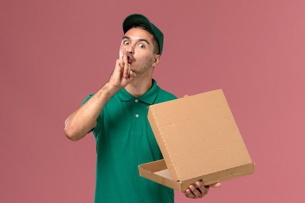 Männlicher kurier der vorderansicht in der grünen uniform, die nahrungsmittelbox hält und es auf rosa hintergrund öffnet