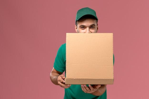 Männlicher kurier der vorderansicht in der grünen uniform, die nahrungsmittelbox hält und sie auf dem hellrosa schreibtisch öffnet