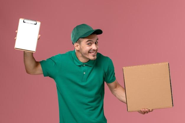 Männlicher kurier der vorderansicht in der grünen uniform, die nahrungsmittelbox zusammen mit notizblock auf dem hellrosa hintergrund hält