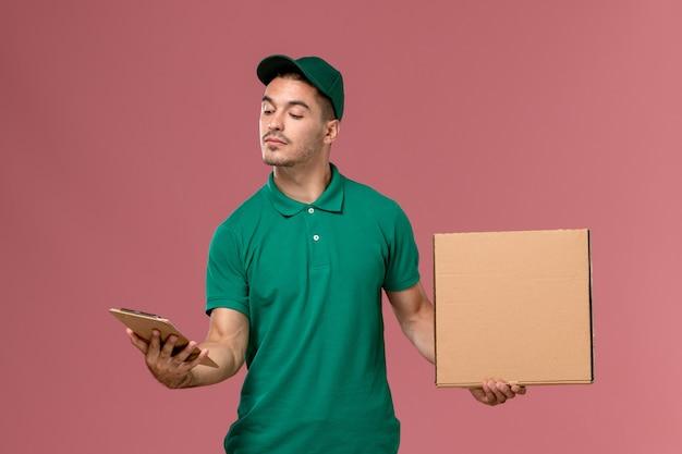 Männlicher kurier der vorderansicht in der grünen uniform, die nahrungsmittelbox zusammen mit notizblock auf dem rosa schreibtisch hält