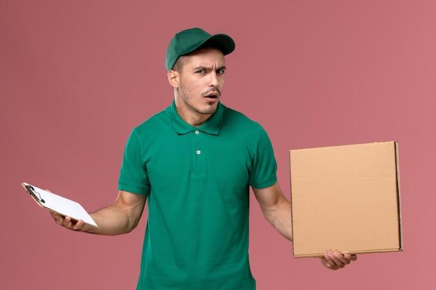 Männlicher kurier der vorderansicht in der grünen uniform, die nahrungsmittelbox zusammen mit notizblock auf rosa boden hält