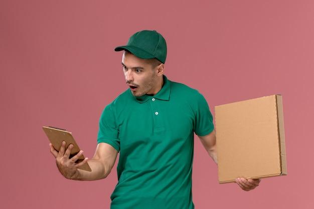 Männlicher kurier der vorderansicht in der grünen uniform, die nahrungsmittelbox zusammen mit notizblock auf rosa hintergrund hält