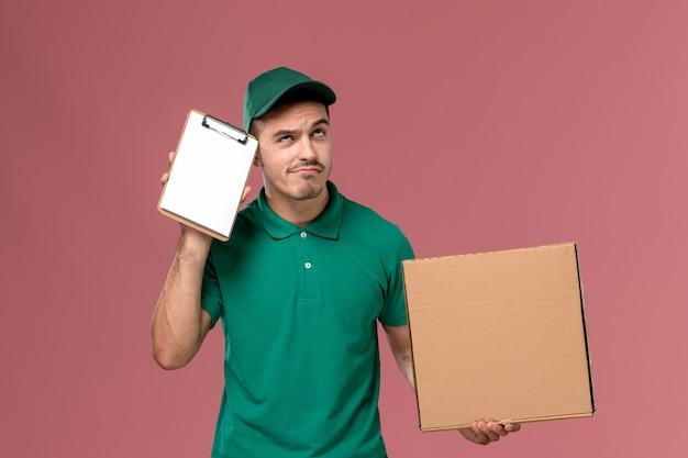 Männlicher kurier der vorderansicht in der grünen uniform, die nahrungsmittelbox zusammen mit notizblock denkt auf hellrosa hintergrund hält