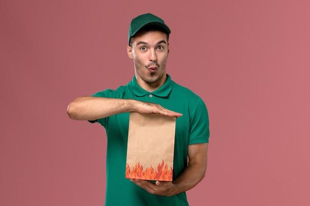 Männlicher kurier der vorderansicht in der grünen uniform, die papiernahrungsmittelpaket auf dem rosa hintergrund hält