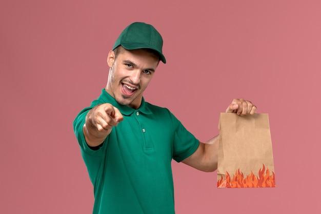 Männlicher kurier der vorderansicht in der grünen uniform, die papiernahrungsmittelpaket hält und auf hellrosa hintergrund hinweist