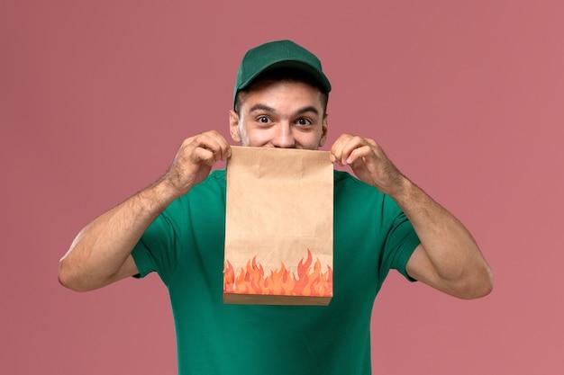 Männlicher kurier der vorderansicht in der grünen uniform, die papiernahrungsmittelpaket hält und auf rosa hintergrund lächelt