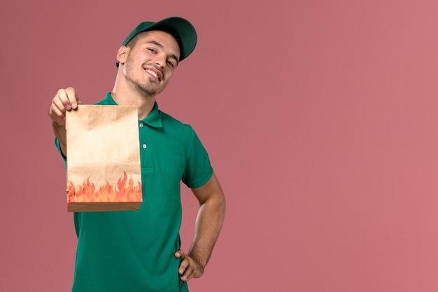 Männlicher kurier der vorderansicht in der grünen uniform, die papiernahrungsmittelpaket hält und einfach auf rosa hintergrund aufwirft