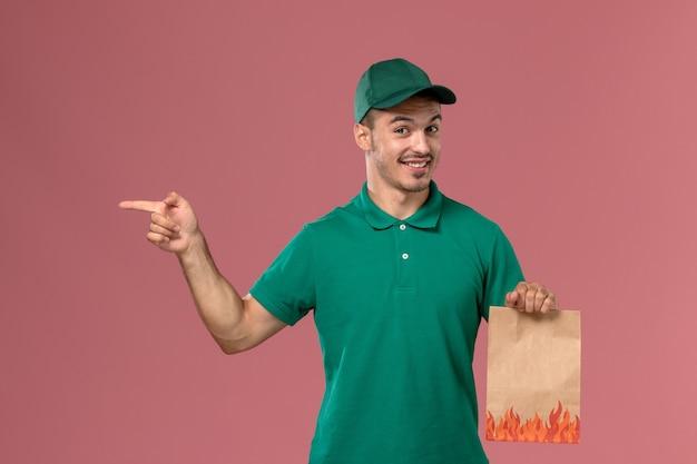 Männlicher kurier der vorderansicht in der grünen uniform, die papiernahrungsmittelpaket mit lächeln auf hellrosa hintergrund hält