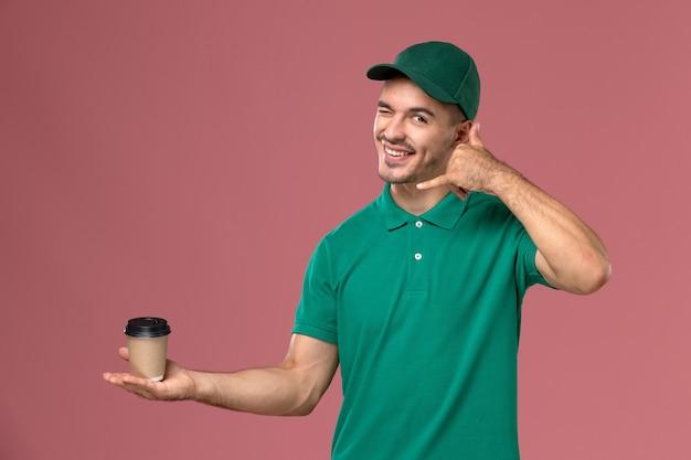Männlicher kurier der vorderansicht in der grünen uniform, die zwinkert und kaffeetasse auf dem rosa hintergrund hält