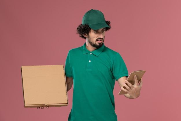 Männlicher kurier der vorderansicht in der grünen uniform und im umhang, der lieferung-lebensmittelbox-notizblock auf der rosa hintergrunddienstuniformlieferung hält