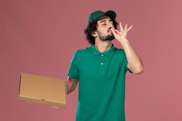Männlicher kurier der vorderansicht in der grünen uniform und im umhang, der nahrungsmittelbox auf rosa hintergrunddienstjobuniformlieferung hält