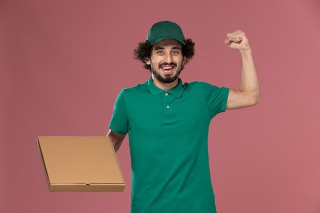 Männlicher kurier der vorderansicht in der grünen uniform und im umhang, der nahrungsmittelbox hält, die auf der rosa hintergrunddienstarbeitsjobuniformlieferung beugt