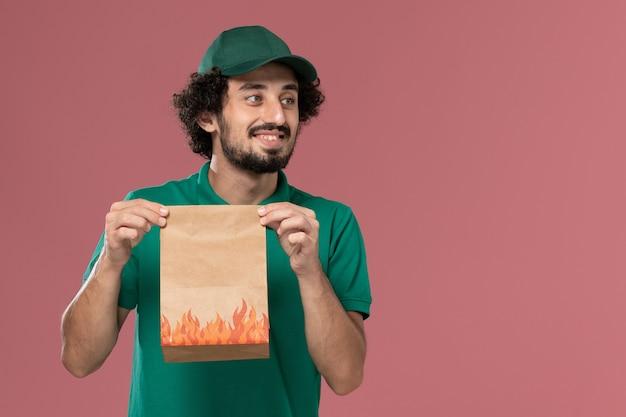 Männlicher kurier der vorderansicht in der grünen uniform und im umhang, der papiernahrungsmittelpaket auf rosa hintergrunddienstarbeiteruniformlieferarbeitsmann hält
