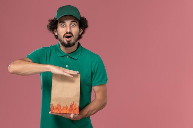 Männlicher kurier der vorderansicht in der grünen uniform und im umhang, der papiernahrungsmittelpaket auf rosa hintergrunddienstuniformlieferauftrag hält