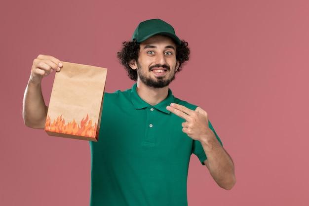 Männlicher kurier der vorderansicht in der grünen uniform und im umhang, der papiernahrungsmittelpaket hält, das auf hellrosa hintergrunddienstarbeiteruniformlieferungsarbeit männlich lächelt