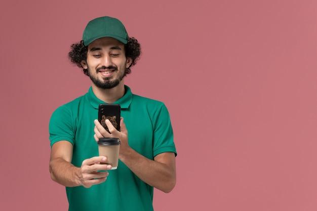 Männlicher kurier der vorderansicht in der grünen uniform und im umhang, die kaffeetasse halten, die foto davon auf rosa hintergrunduniform-lieferservice macht