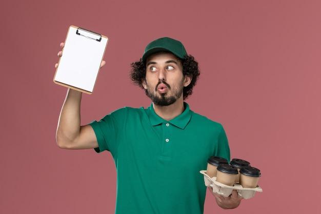Männlicher kurier der vorderansicht in der grünen uniform und im umhang, die kaffeetassen mit notizblock auf dem rosa hintergrunddienstuniform-lieferjob männlich halten