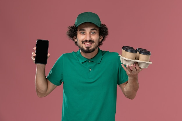 Männlicher kurier der vorderansicht in der grünen uniform und im umhang, die kaffeetassen mit telefon auf dem hellrosa hintergrunddienstuniformlieferauftrag halten