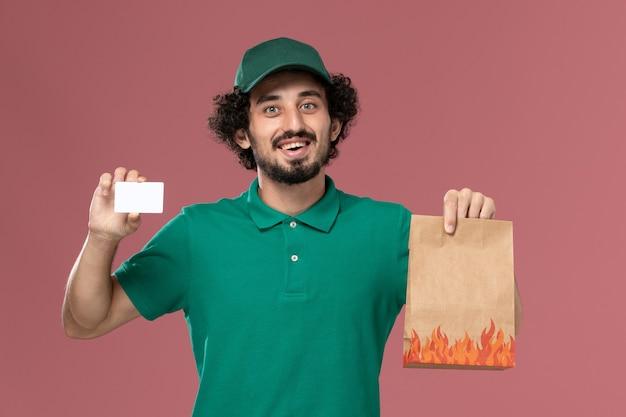 Männlicher kurier der vorderansicht in der grünen uniform und im umhang, die karte und lebensmittelpaket auf der rosa hintergrunddienstuniformlieferung männlicher jobarbeit halten