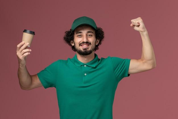 Männlicher kurier der vorderansicht in der grünen uniform und im umhang, die lieferkaffeetasse halten und auf dem rosa hintergrunduniformlieferdienstfirmenjobarbeiter biegen