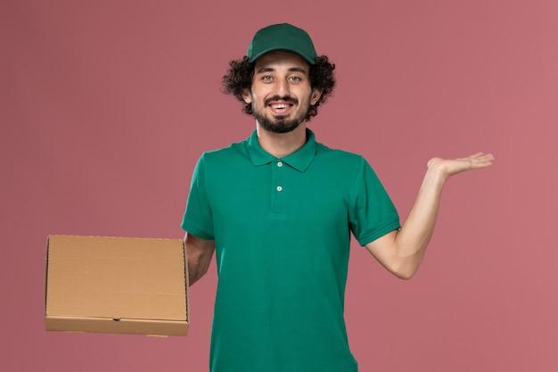 Männlicher kurier der vorderansicht in der grünen uniform und im umhang, die nahrungsmittelbox halten und auf der rosa hintergrunddienstarbeiterjobuniformlieferung lächeln