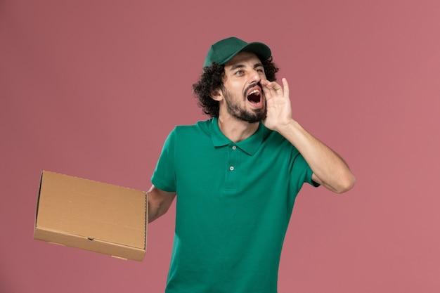Männlicher kurier der vorderansicht in der grünen uniform und im umhang, die nahrungsmittelbox halten und auf der rosa hintergrunddienstarbeiterjobuniformlieferung schreien