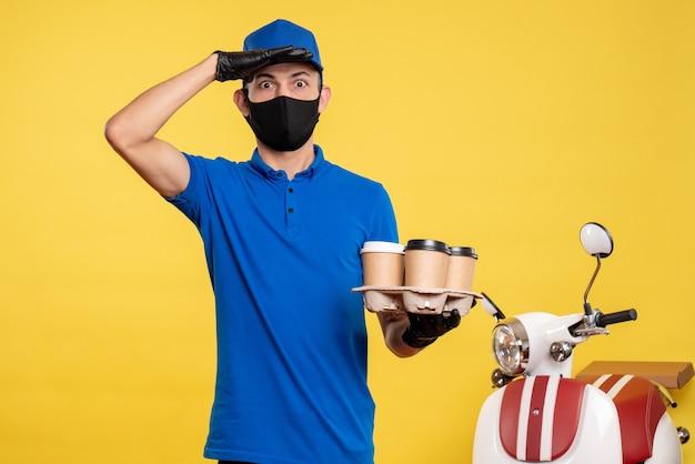Männlicher kurier der vorderansicht in der maske, die kaffee auf gelber job-covid-service-lieferuniformarbeit hält