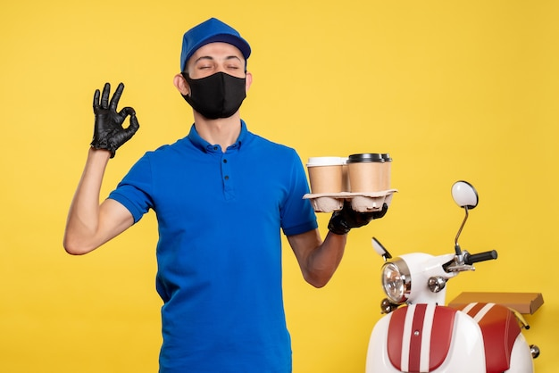 Männlicher kurier der vorderansicht in der maske, die kaffee auf uniformarbeit der gelben job-covid-pandemie-lieferung hält