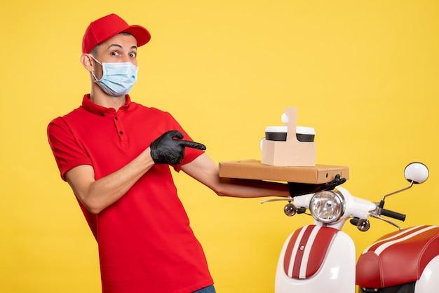 Männlicher kurier der vorderansicht in der maske mit lieferkaffee und -schachtel auf der arbeitsuniform des gelben service covid pandemic color virus