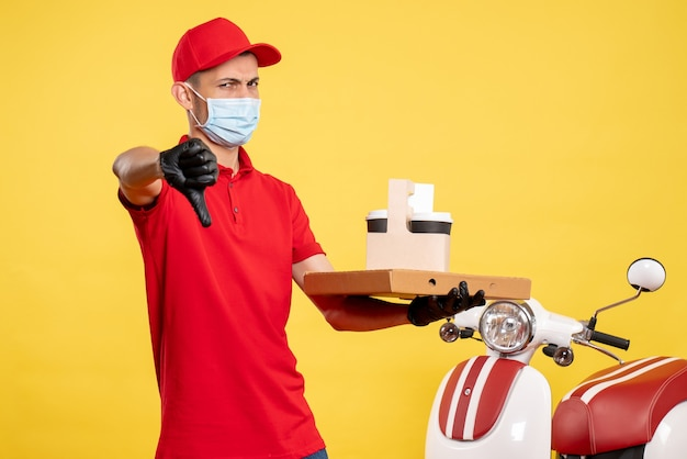 Männlicher kurier der vorderansicht in der maske mit lieferkaffee und -schachtel auf gelbem dienstjob coviduniform pandemisches farbvirus