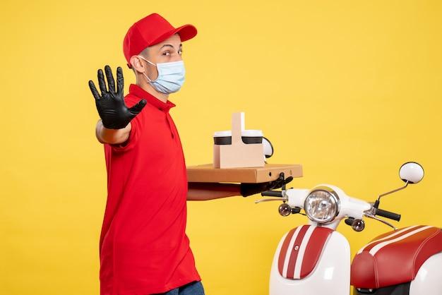 Männlicher kurier der vorderansicht in der maske mit lieferkaffee und -schachtel auf gelbem service-covid-uniform-pandemie-farbvirusjob