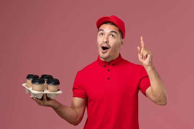 Männlicher kurier der vorderansicht in der roten uniform, die braune kaffeetassen der lieferung auf hellrosa boden hält