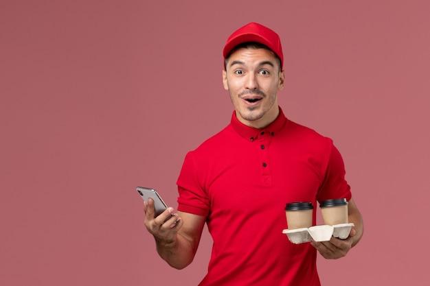 Männlicher kurier der vorderansicht in der roten uniform, die braune kaffeetassen der lieferung hält und ein telefon an der hellrosa wand verwendet