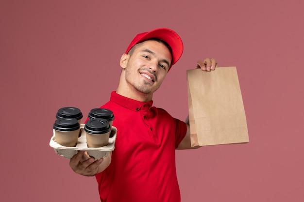 Männlicher kurier der vorderansicht in der roten uniform, die braune kaffeetassen der lieferung mit lebensmittelpaket auf rosa bodenservice-zustelljobarbeiteruniform hält